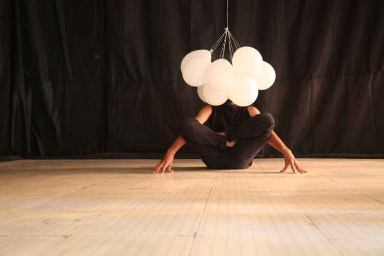 person in yoga position with balloons