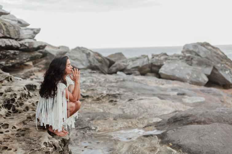 photo of woman sitting on rock