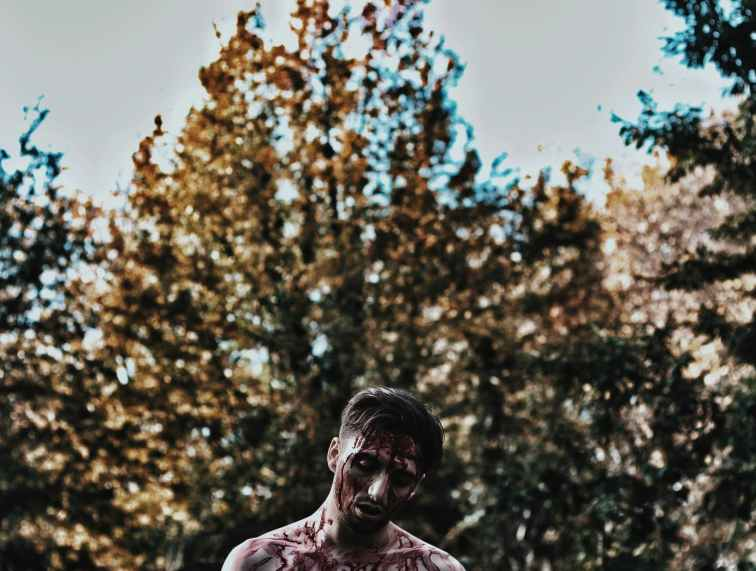 photo of man full of blood near trees
