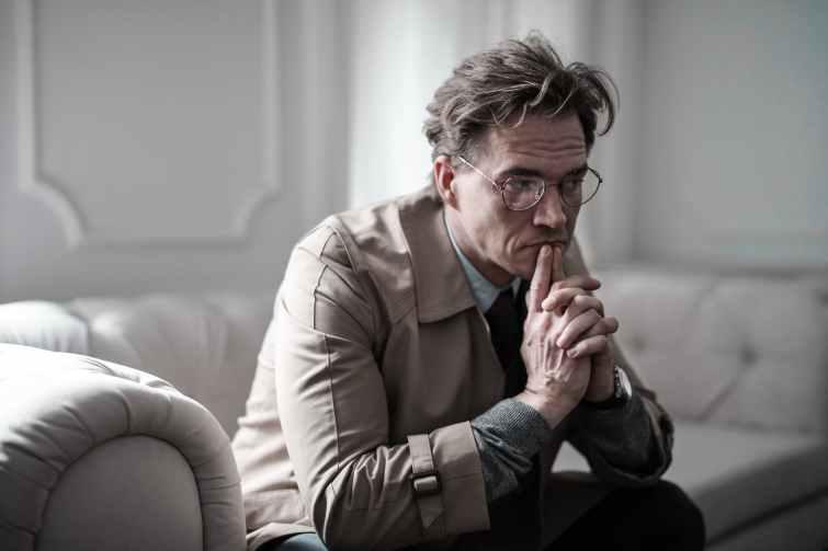 man in brown suit jacket sitting on white sofa