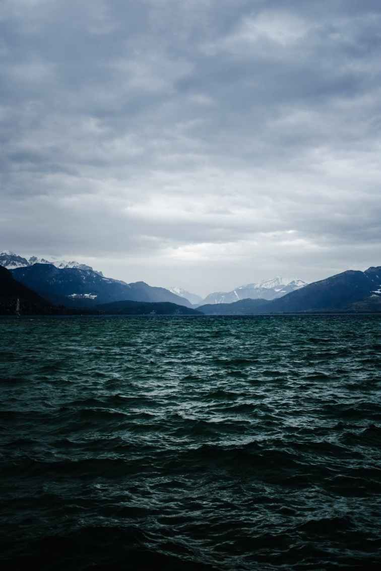 body of water near mountain under cloudy sky