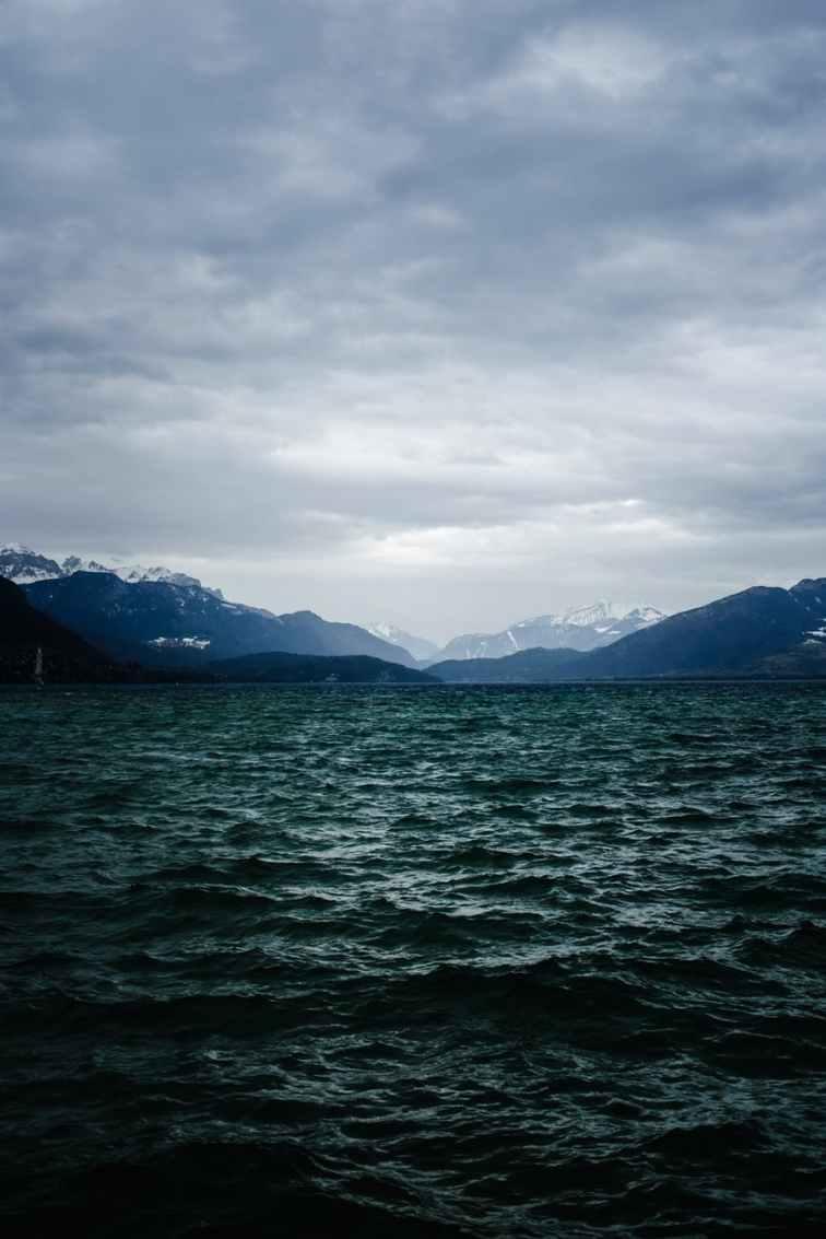 body of water near mountain under cloudy sky