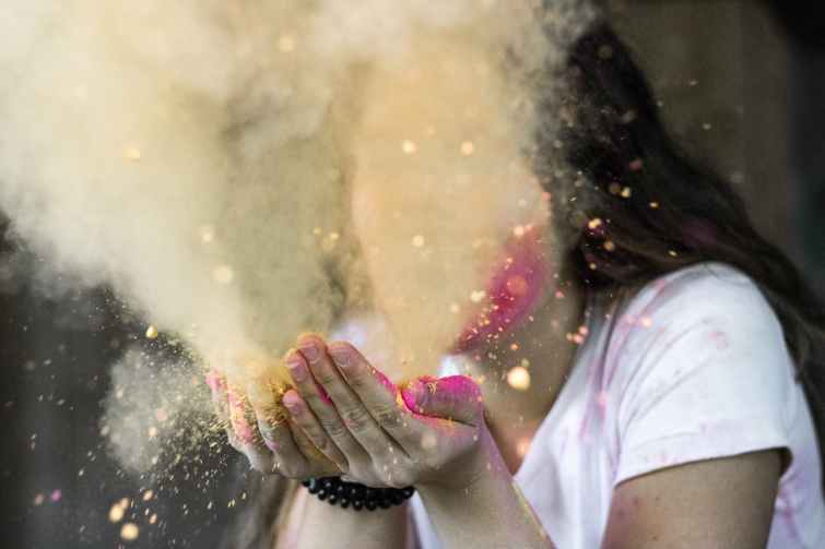 woman in white cap sleeved shirt blowing dust